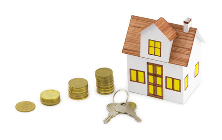Mortgage concept. Closeup view of small toy house with keys and golden coins isolated on white background