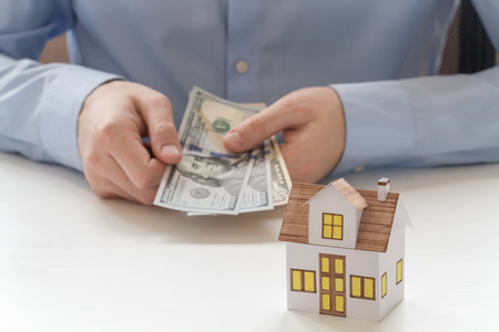 Mortgage concept. Closeup view of businessman holding fan of one hundred dollar bills in hands and sitting at the white wooden table with small toy house