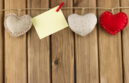 Love story concept. Soft hearts with blank note paper hanging on the clothesline on wooden background Standard-Bild