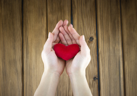Love story concept. Top view of female hands holding red heart shape on wooden background