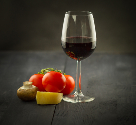 Vegetables and glass of vine on dark wooden background