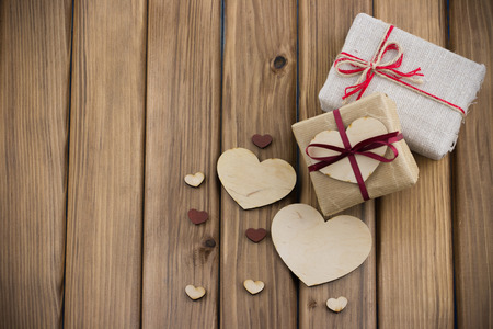 Valentines Day concept. Gift boxes with red ribbon with small wooden hearts on old vintage wooden background Standard-Bild