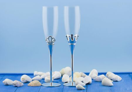Wedding glasses with shells on wooden vintage blue background photo