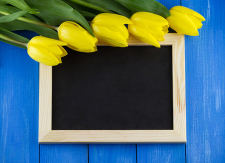 Top view of yellow tulips with empty blackboard on blue wooden background Stock Photo