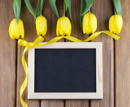 Top view of yellow tulips and blank blackboard with curly ribbon on wooden background