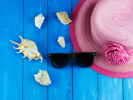 Top view of pink woven hat with sunglasses and white shells on blue wooden background Standard-Bild