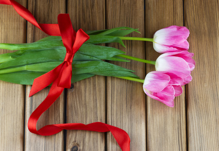 Top view of pink tulips with red ribbon and bow on wooden background
