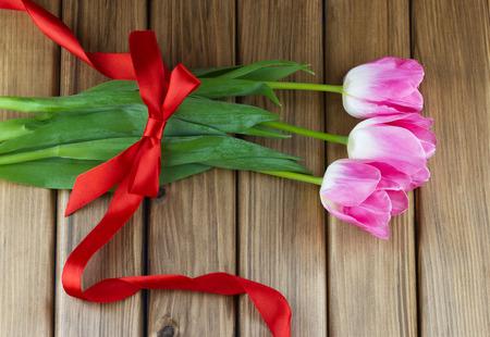 Vista superior de tulipanes de color rosa con cinta roja y arco sobre fondo de madera Foto de archivo - 41429056