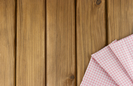 Top view of pink checkered napkin in the corner on wooden background with place for your text Standard-Bild