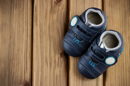 Top view of little boy shoes in the corner on wooden background with place for your text