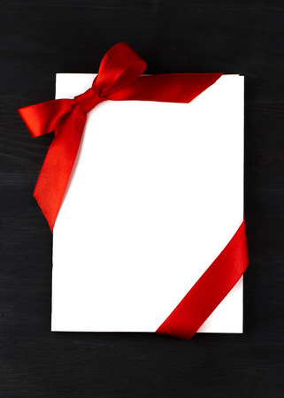 Top view of white holidays gift card with red bow on dark wooden background