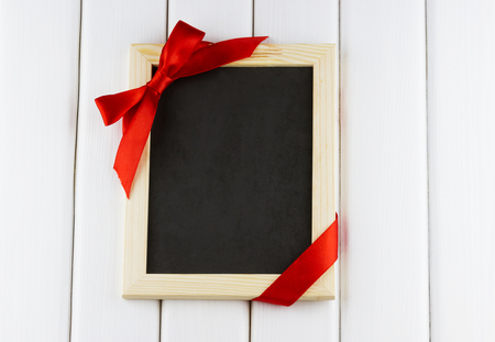 Top view of empty blackboard decorated red bow and ribbon on white wooden background Standard-Bild