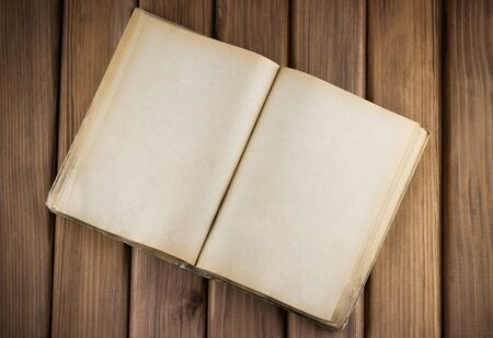 Top view of blank open old book with grange pages on wooden background Standard-Bild