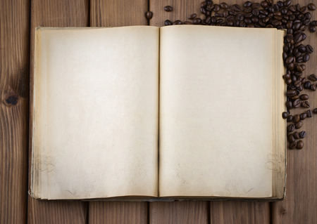 Top view of blank old book with cofee beans on vintage wooden table Stock Photo