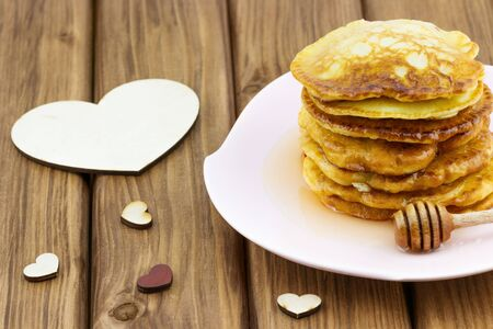 Stack of pancakes with honey on the plate with hearts on wooden background