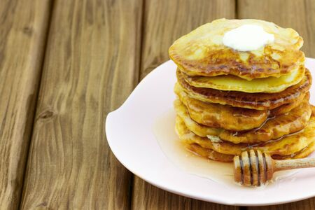 Stack of pancakes with honey and piece of butter on wooden table
