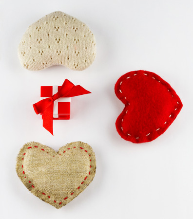 Small red gift box and different soft hearts on white background Stock Photo