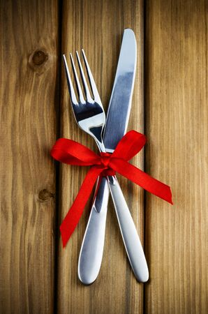 Romantic dinner concept. Top view of silver fork and knife decorated red ribbon with bow on wooden background Standard-Bild