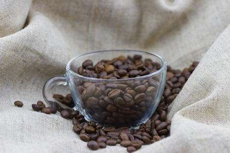 Closeup view of roasted coffee beans in the cup on sackcloth