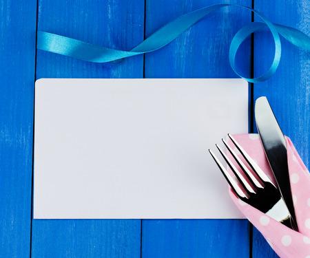 Concepto Cena romántica. Vista superior de la hoja de papel en blanco con tenedor y cuchillo de plata decorada rizado cinta azul sobre fondo de madera Foto de archivo - 41429103
