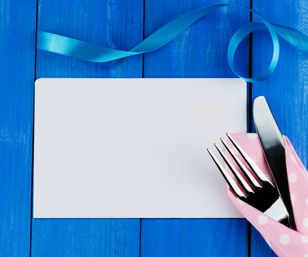 Romantic dinner concept. Top view of blank sheet of paper with silver fork and knife decorated blue curly ribbon on wooden background