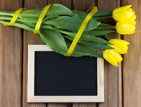 Top view bouquet of yellow tulips with blank blackboard on wooden background