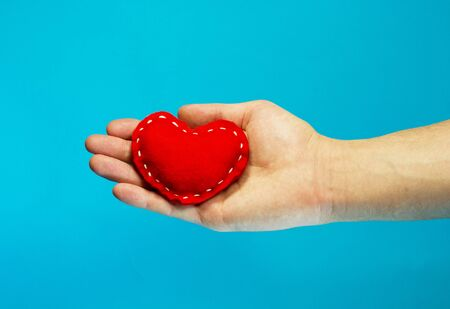 Red heart in old senior woman hand on blue background