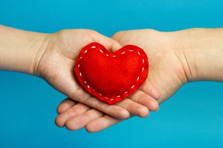 holiday symbol: Couple in love concept. Red heart in woman and man hands on blue background