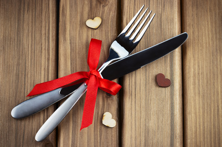 Closeup view of silver fork and knife decorated red bow with hearts on wooden background