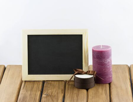 Empty blackboard with purple candle and gift box on wooden background photo