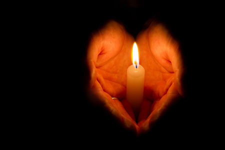 Man hands holding a burning candle on dark background Foto de archivo