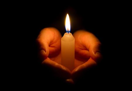 Man hands holding a burning candle on dark background Standard-Bild