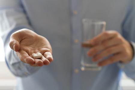 droga: Opini�n del primer de p�ldoras hombre que sostiene en una mano y un vaso de agua en el otro lado