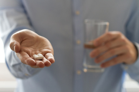 Closeup view of man holding pills in one hand and glass of water in the another hand