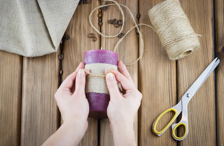 make a gift: How to make candle concept. Top view of female hands make candle decorated with sackcloth and twine on wooden background