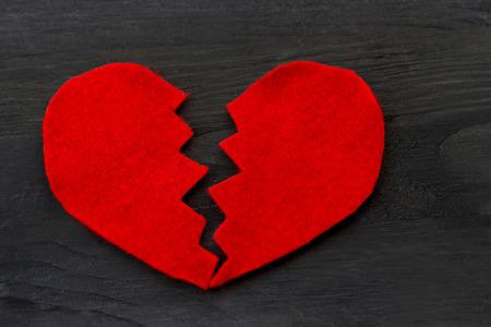 corazon roto: Concepto del amor historia. Vista superior de color rojo en forma de corazón roto en el fondo de madera