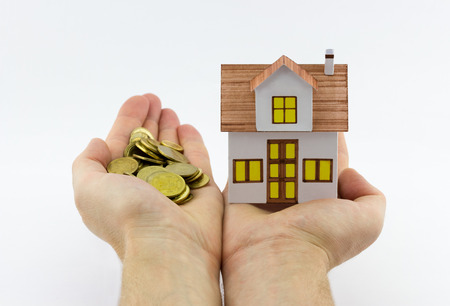 Mortgage concept. Closeup view of man holding small toy house in one hand and golden coins in the another hand on white background Stock Photo