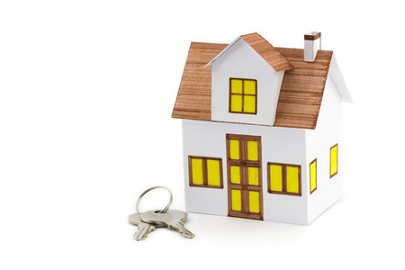 Mortgage concept. Closeup small toy house with keys isolated on white background