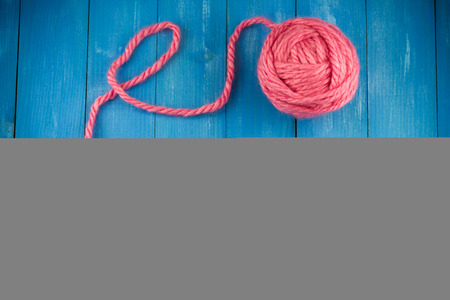sewing item: Pink woolen yarn ball and knitting needles on old vintage blue wooden background
