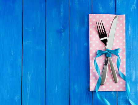 Romantic dinner concept. Top view of silver fork and knife decorated blue curly ribbon with bow on wooden background