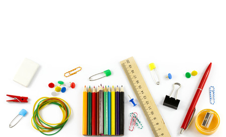 School supplies: colored pencils wooden yardstick erasers binders stationery gum paper clips pencil sharpener a small clothespin colored pins and pen isolated on white background photo