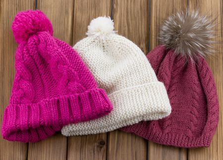 warm clothes: Set of colored knit wool hat with pom pom on wooden nackground Stock Photo