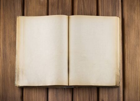 Top view of blank open old book with grange pages on wooden table