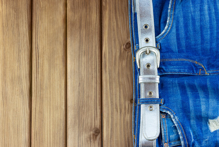 WEIGHT: Top view of female jeans with belt on wooden background with place for your text