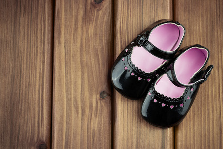 Top view of little girl shoes with hearts on wooden background photo