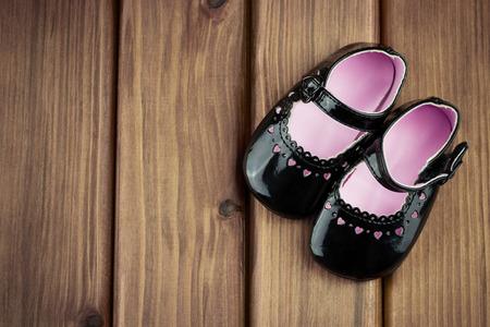 Vista superior de pequeños zapatos de la muchacha con los corazones en el fondo de madera