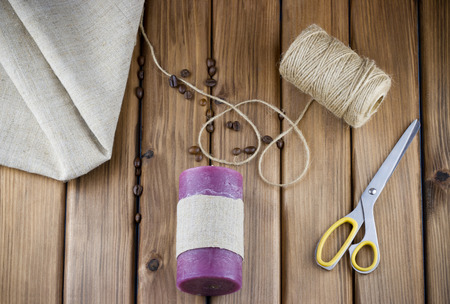 make a gift: Top view of purple candle decorated with sackcloth and twine on wooden background