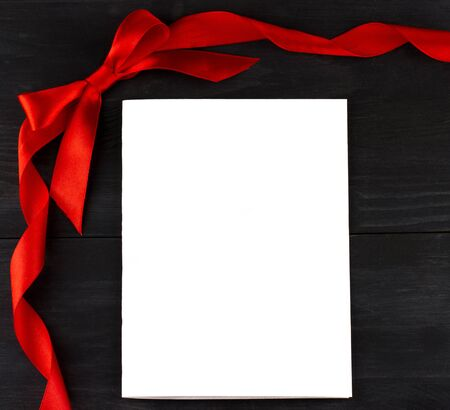 black wood texture: op view of white sheet of paper with red ribbon and bow on dark wooden background