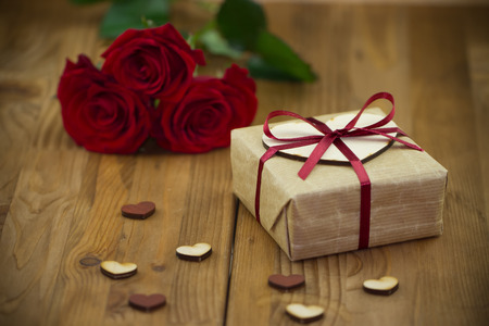 heart shaped stuff: Valentines Day concept. Red roses and gift box tied red ribbon with small wooden hearts on old vintage wooden background
