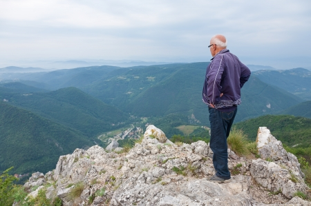 man looking at sky: Elderly man standing on the edge of a clif